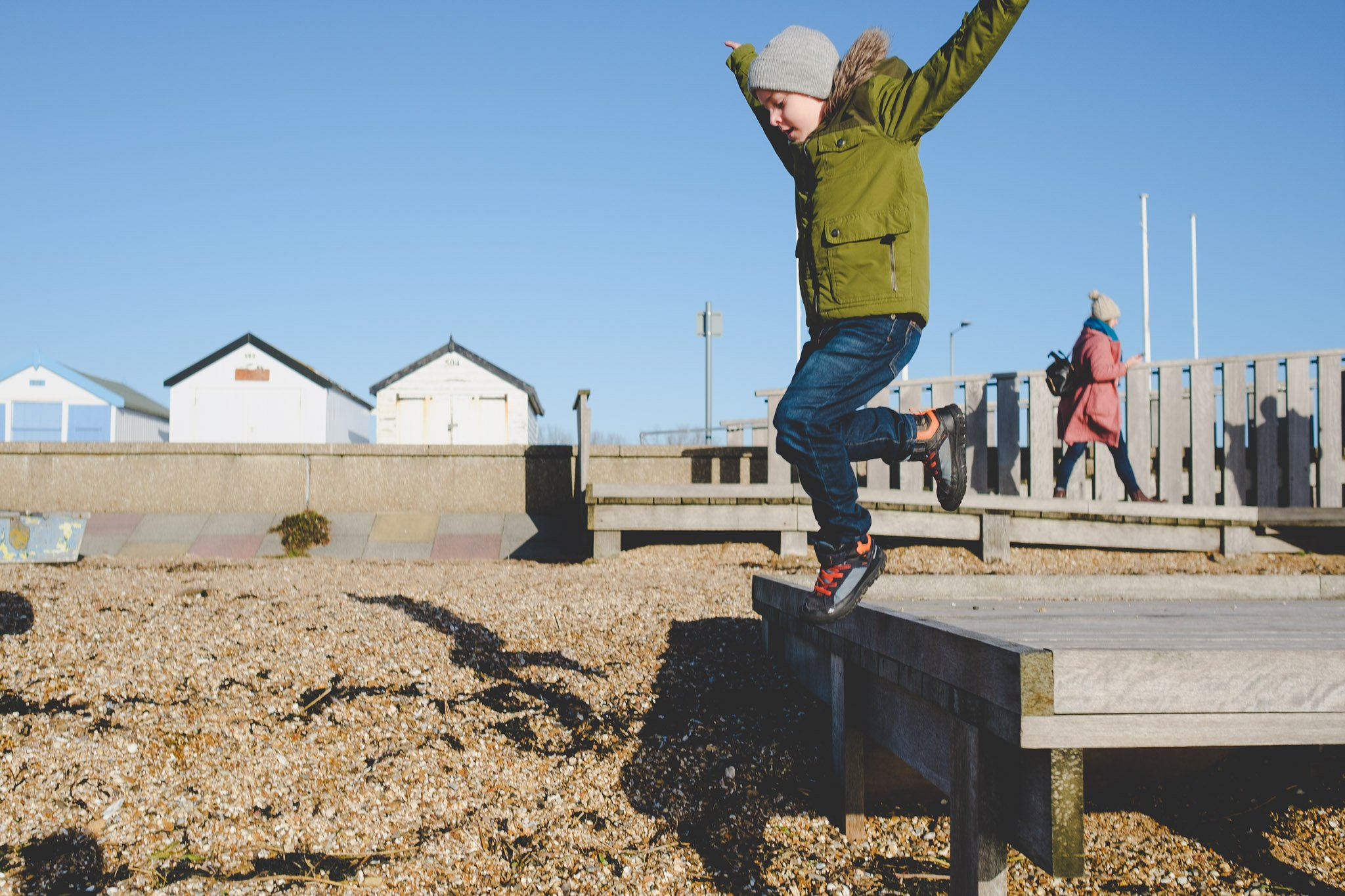 Young boy jumping onto Shoeburyness beach. Photography by thatthingyoupluck